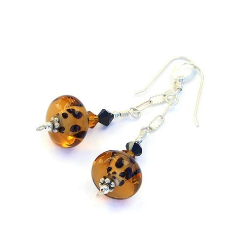 The lampwork glass beads used in the handmade earrings were created with a core of light amber glass and black spots encased by a darker amber glass - glowing beauties!