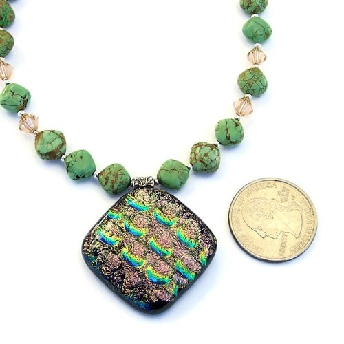 "The ""Magical"" handmade dichroic pendant necklace shown with a quarter for size comparison."